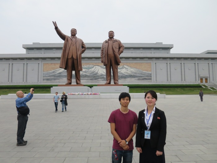 With our North Korean guide Ms. Jong and the statues of Kim Il-Sung and Kim Jong-il at Munsudae Hill in Pyongyang.